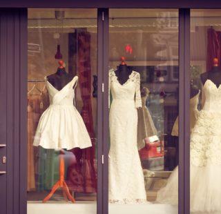 Wedding dresses displayed in a shop window.