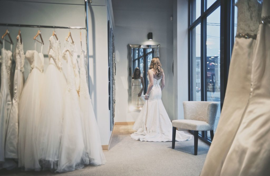 Bride looks in a large mirror as she tries on a wedding gown.
